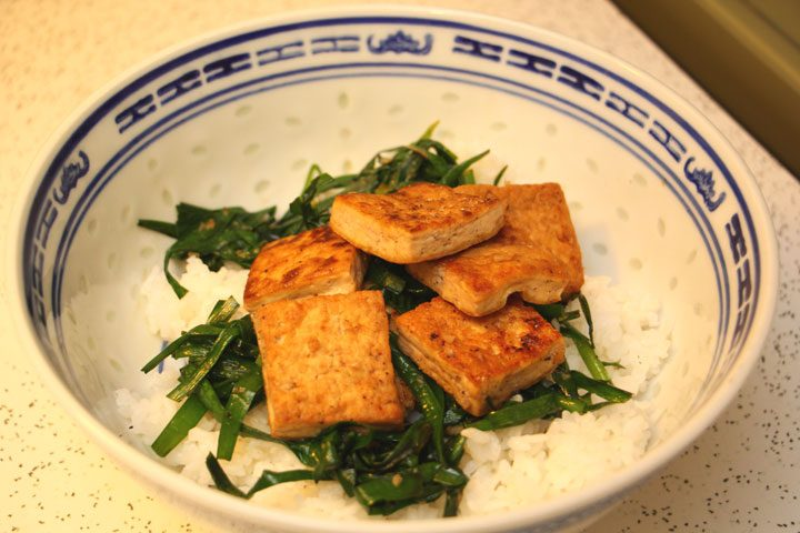 fried tofu on a bed of chives and garlic atop white rice in blue and white ceramic bowl.