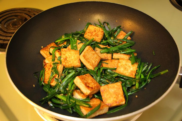 easy fried tofu with garlic and chinese chives recipe on stovetop in wok.