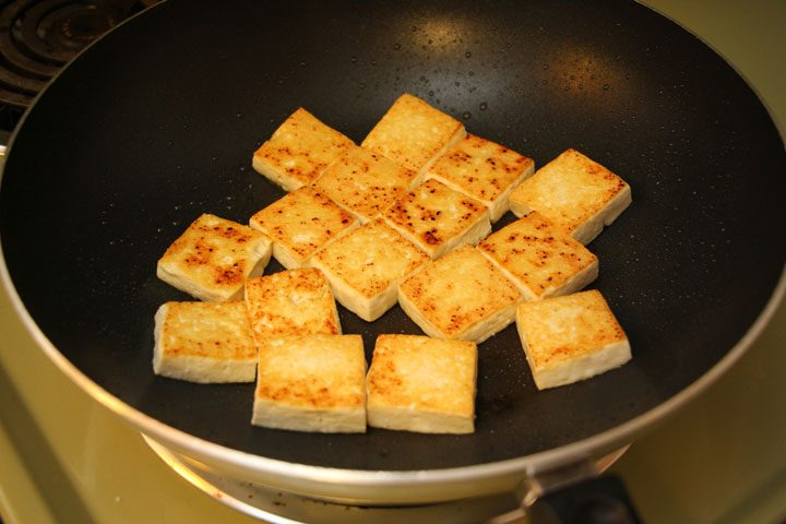 cubes of soft tofu frying on stovetop.
