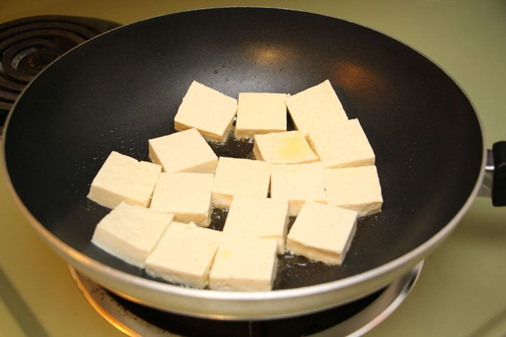 Cubes of tofu sitting in oil on stovetop to be fried