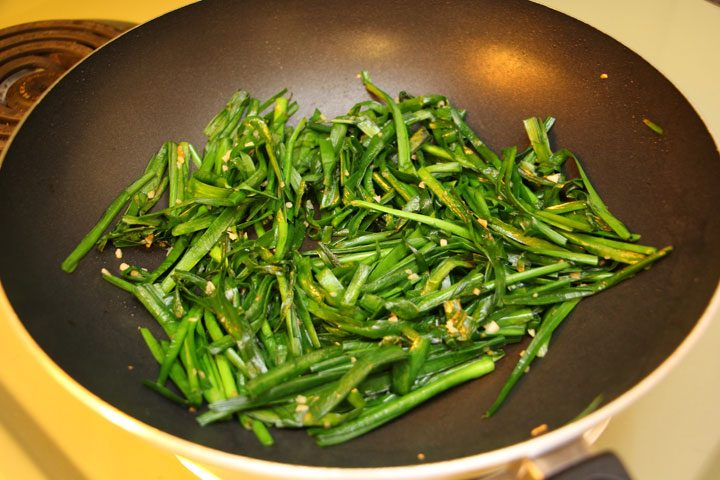 chinese chives and garlic being cooked.