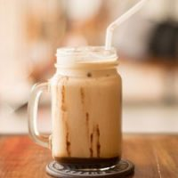 Starbucks copycat frappucino recipe in mason jar with drizzle of mocha chocolate.