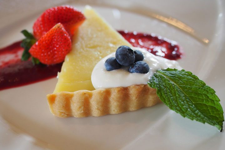 lemon tart pie slice with mint, blueberries, strawberries, berry sauce