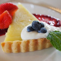 lemon tart slice with mint, fresh berries, sauce, whipped topping