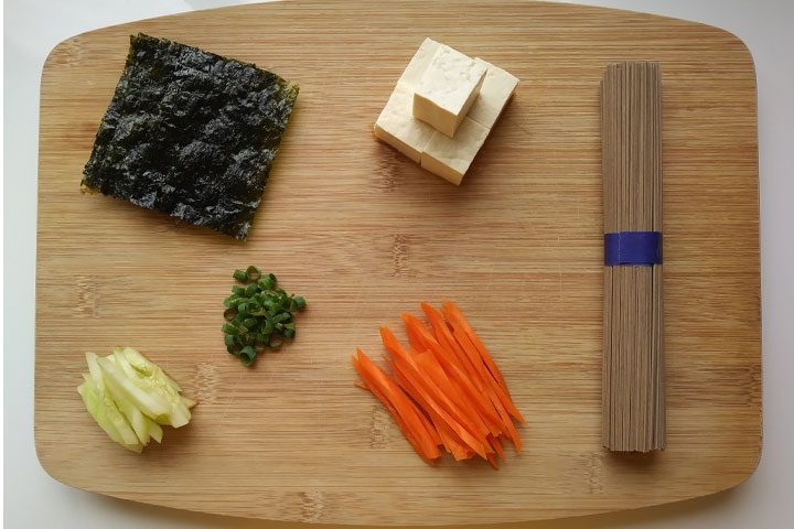ingredients for asian japanese cold soba noodle salad recipe on bamboo cutting board
