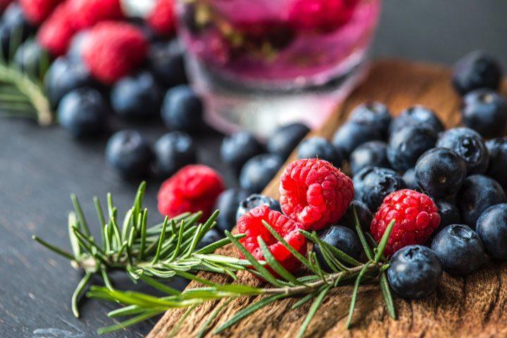 raspberries, blueberries, rosemary on cutting board