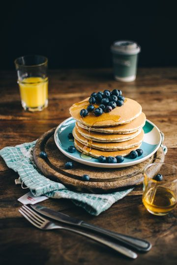 stack of pancakes topped with blueberries with juice on side