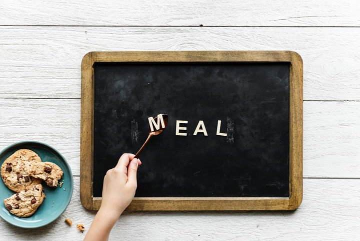 letters spelling meal placed on chalkboard with spoon