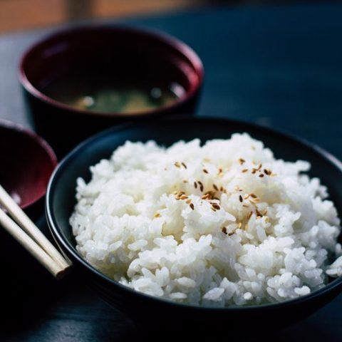 bowl of perfect white rice in black bowl with miso soup on side.