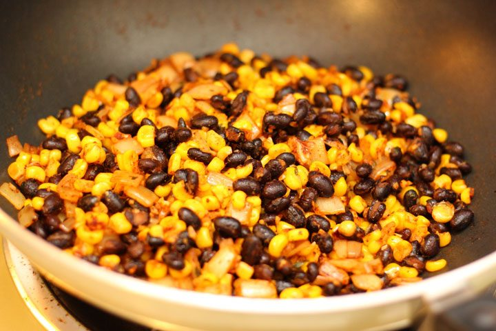 tex mex mix of black beans, onions, corn cooking on stovetop