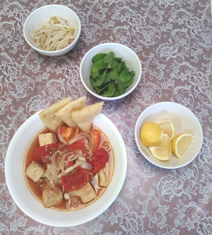vietnamese tomato soup with rice noodles, bean sprouts, basil, lemon wedges
