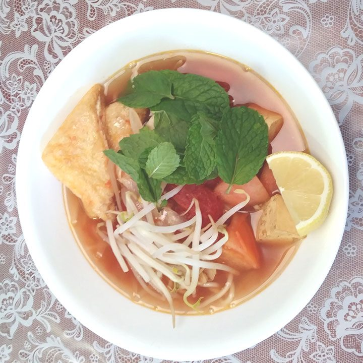 top view of vietnamese tomato soup with rice noodles