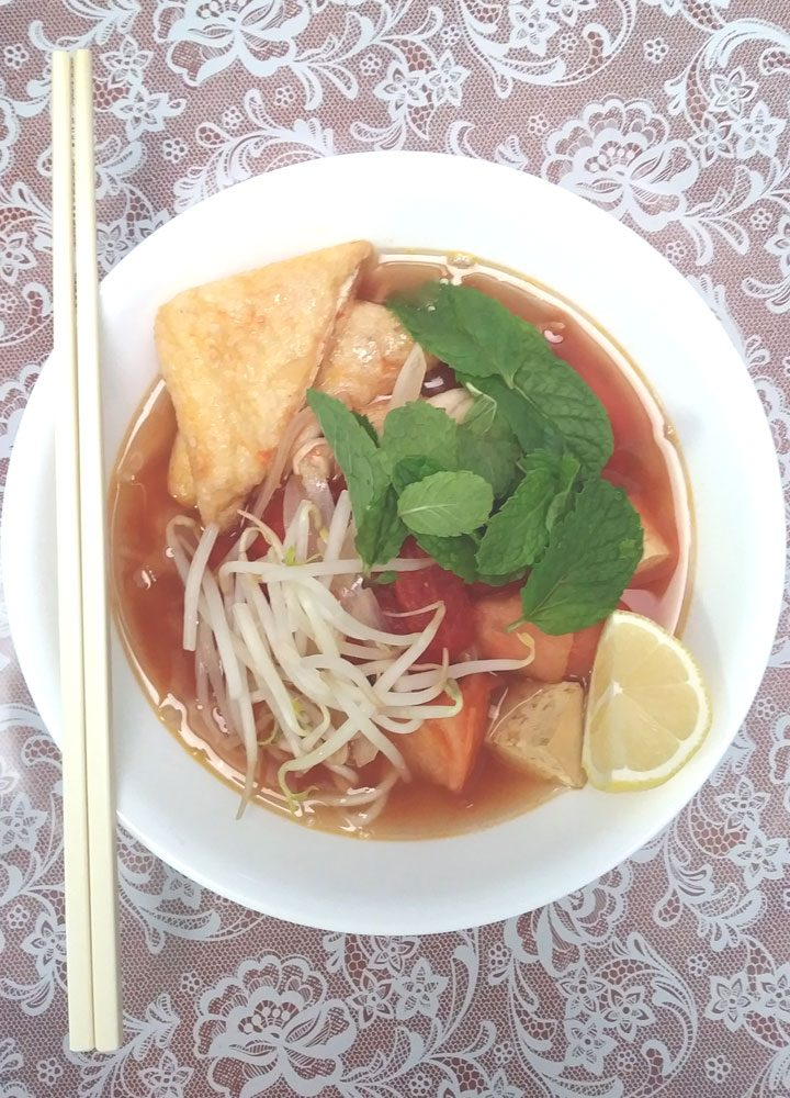vegan bun rieu chay vietnamese tomato soup with rice noodles and pair of chopsticks