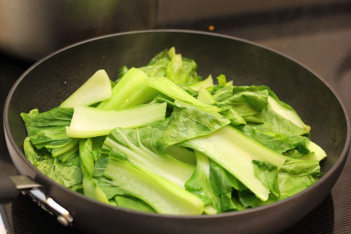 vegan tonkotsu soy milk ramen bok choy on stove for a little green to noodle dish.