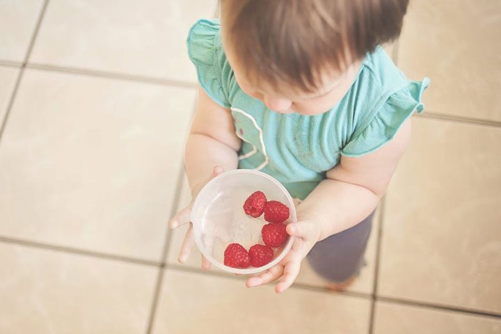 little child holding bowl of raspberries