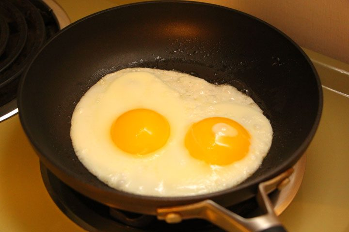 vegetarian loco moco recipe - 2 large eggs frying in non-stick pan on top of stove - sunny side up