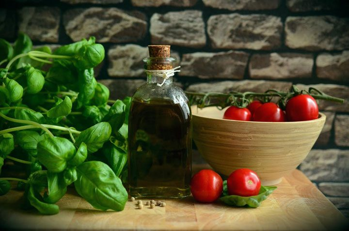 ingredients for marinara sauce - basil, olive oil, fresh vine tomatoes